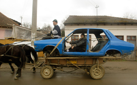 A man rides a horse-drawn cart carrying an old Dacia vehicle for sale as scrap iron in Telega, 100km (62 miles) north of Bucharest, March 6, 2008.   REUTERS/Radu Sigheti (ROMANIA)